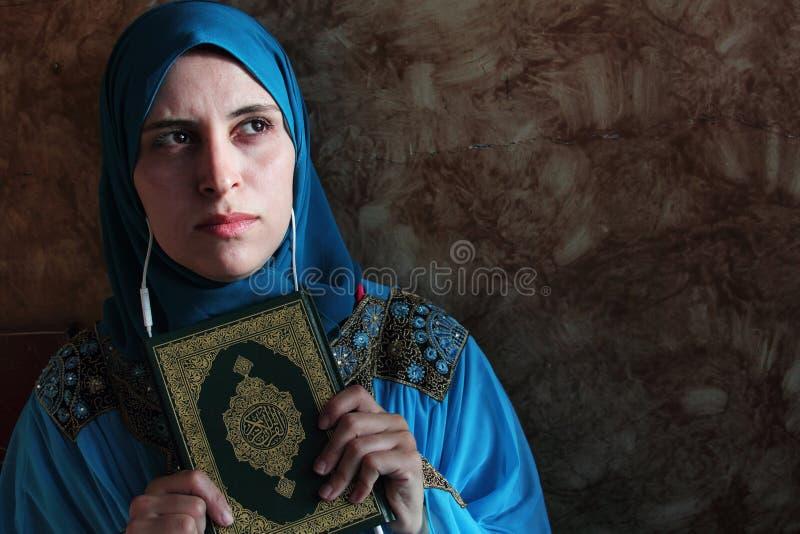 Arabisk muslimkvinna med boken och hörlurar med mikrofon för Koranen den islamiska heliga arkivbilder