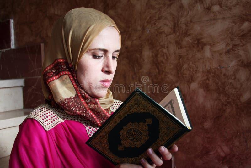 Arabisk muslimkvinna med den heliga boken för Koranen royaltyfria bilder
