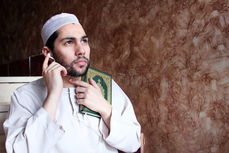Arabisk muslimman med boken och hörlurar med mikrofon för Koranen den islamiska heliga royaltyfri foto