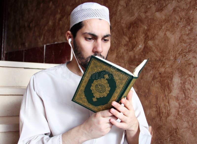 Arabisk muslimman med boken och hörlurar med mikrofon för Koranen den islamiska heliga arkivbild