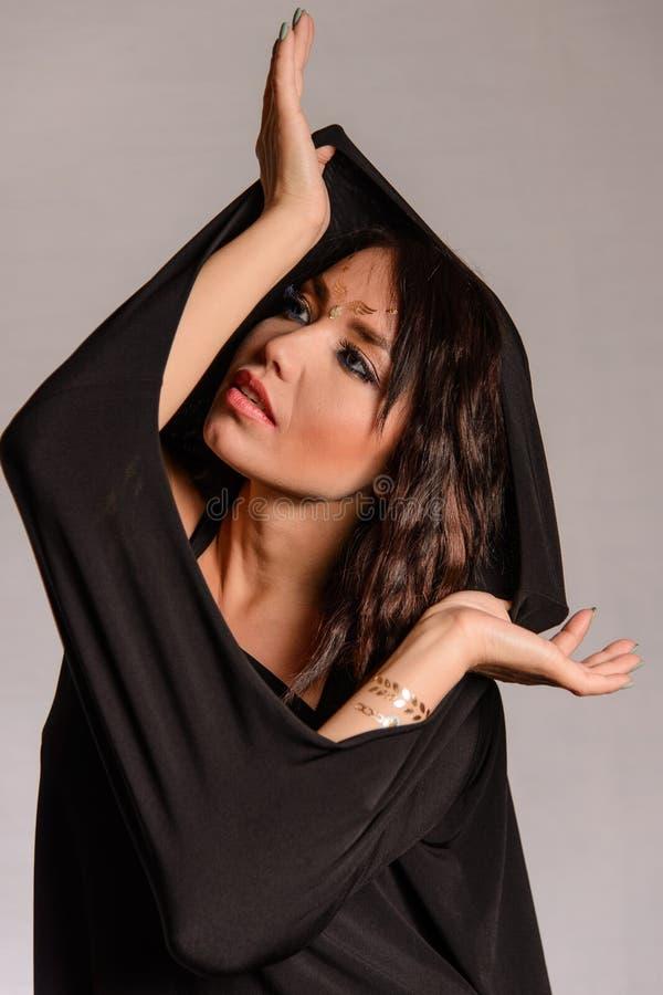 Arabisk muslimsk flicka som bär den svarta ämbetsdräkten arkivfoto