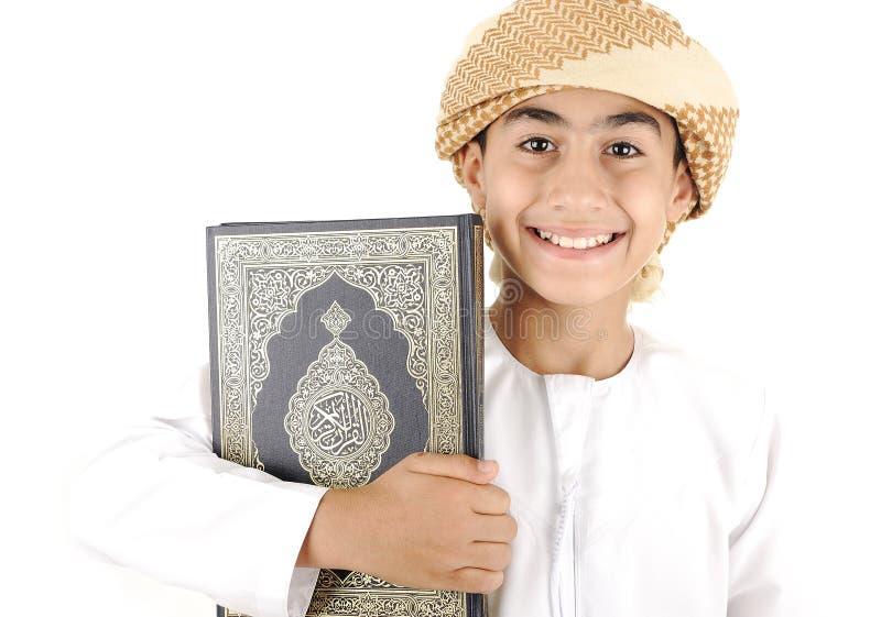 Arabisk pojke med Koranen royaltyfri foto