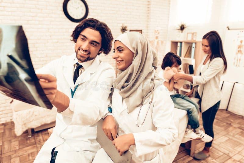 Arabisk röntgenstrålefilm för doktor Appointment Holding Arabiska Pediatriciansdoktorer för medicinsk konsultation Muslimska dokt arkivbild