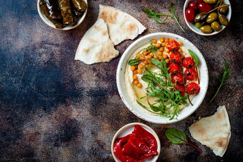 Arabisk traditionell kokkonst Mellersta - ?stlig meze med pitabr?det, oliv, hummus, v?lfylld dolma, knipor royaltyfri fotografi