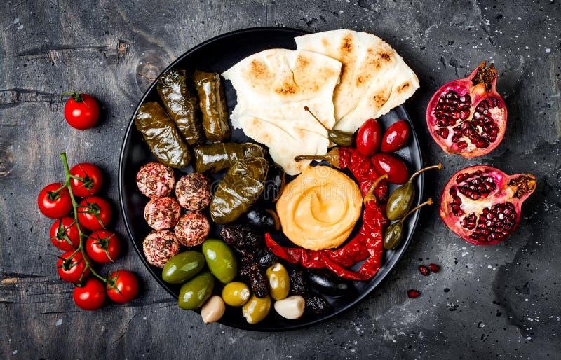 Arabisk traditionell kokkonst Mitt - östligt mezeuppläggningsfat med pitabrödet, oliv, hummus, välfylld dolma, labnehostbollar i  royaltyfria bilder