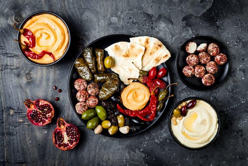 Arabisk traditionell kokkonst Mitt - östligt mezeuppläggningsfat med pitabrödet, oliv, hummus, välfylld dolma, labnehostbollar i  arkivfoto