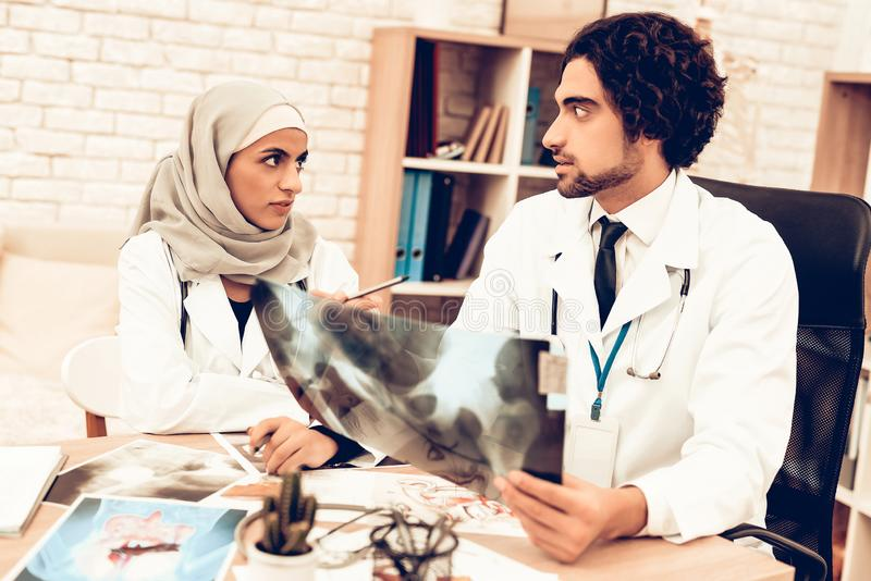 Arabiska doktorer som har konsultation, röntgenstrålefilm royaltyfria foton