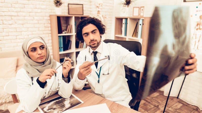Arabiska doktorer som har konsultation, röntgenstrålefilm royaltyfri fotografi