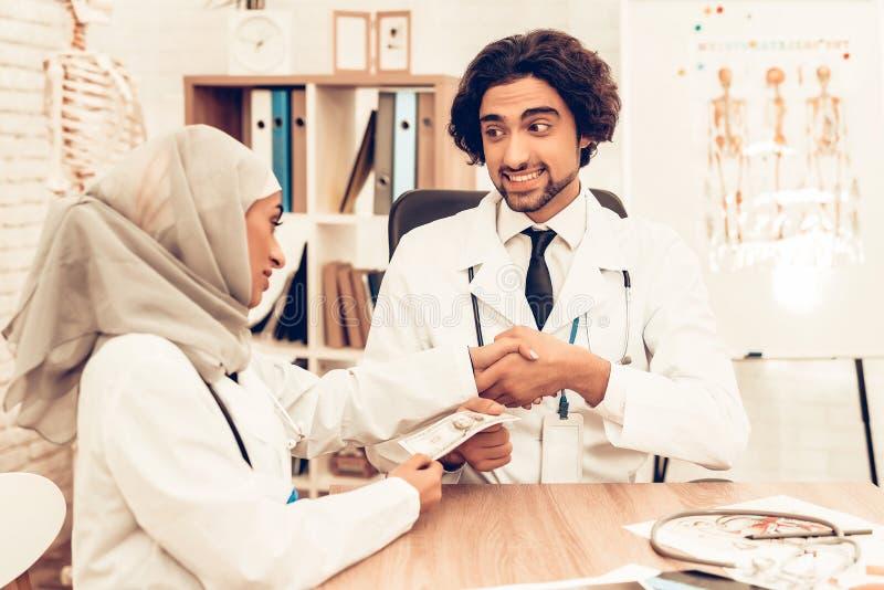 Arabiska doktorer som räknar pengar efter arbete, avlöningsdag royaltyfri bild