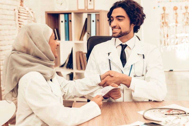 Arabiska doktorer som räknar pengar efter arbete, avlöningsdag royaltyfri fotografi