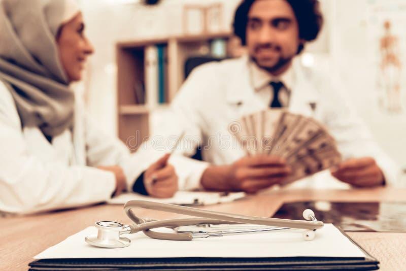 Arabiska doktorer som räknar pengar efter arbete, avlöningsdag royaltyfria foton