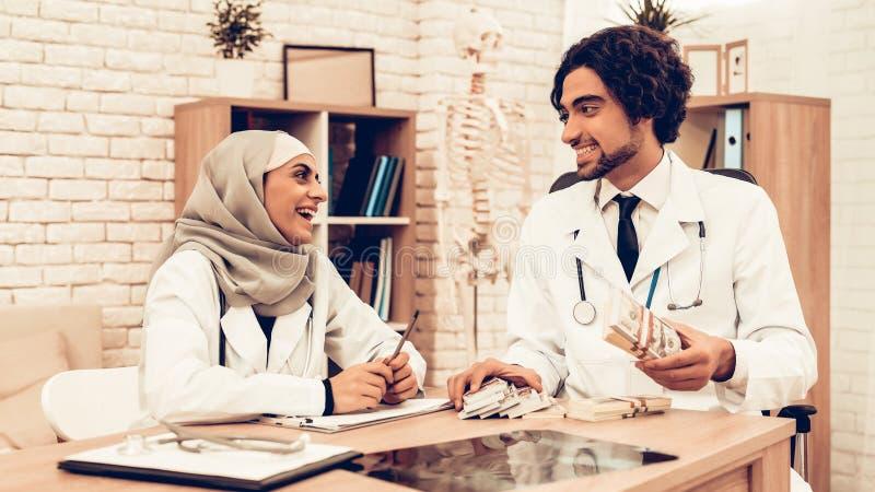 Arabiska doktorer som räknar pengar efter arbete, avlöningsdag royaltyfria bilder