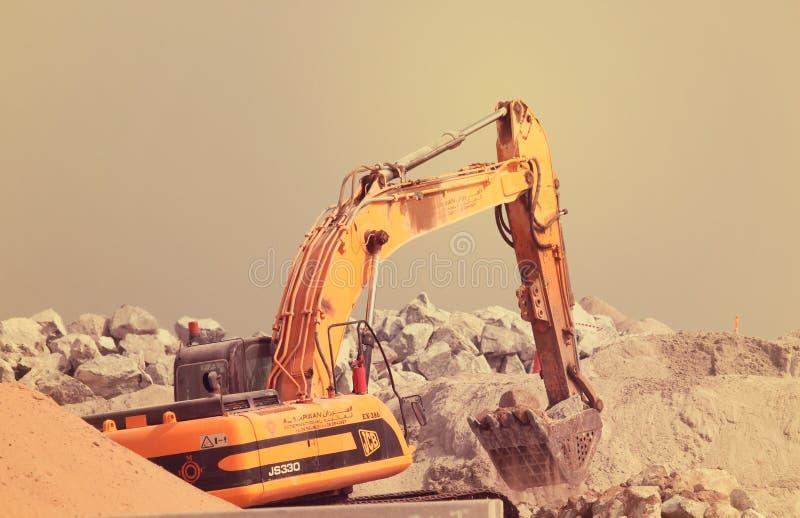 ARABISKA EMIRATER för DUBAI-UNITED PÅ 21 den JUNI 2017 grävskopamaskinen på utgrävningearthmovingarbete i sand i Dubai Förenade A arkivfoto