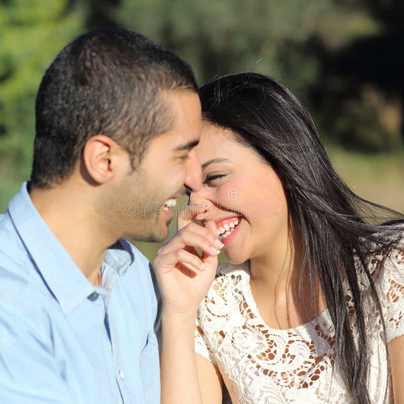 Arabiska tillfälliga par som flörtar att skratta som är lyckligt i en parkera arkivbilder