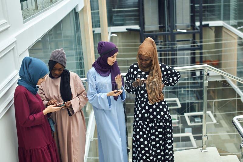 Arabiska unga kvinnor som h?ller ?gonen p? p? det musikaliska videogemet f?r mobiltelefon som tillsammans st?r arkivbilder
