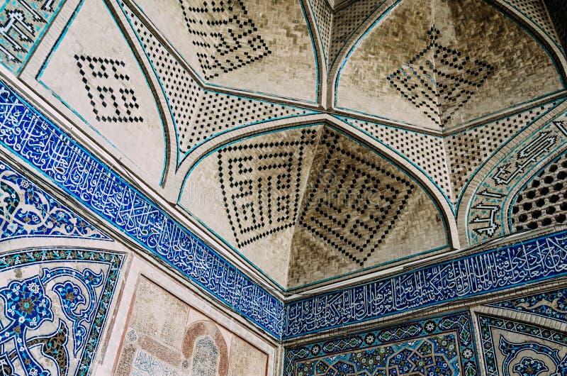 ArabiskaQuranic kalligrafi witten i den Thuluth skriften på polychrome tegelplattor, på hörnet av imamen Mosque royaltyfri bild