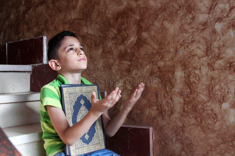 Arabiskt muslimbarn med den heliga boken för Koranen arkivfoto