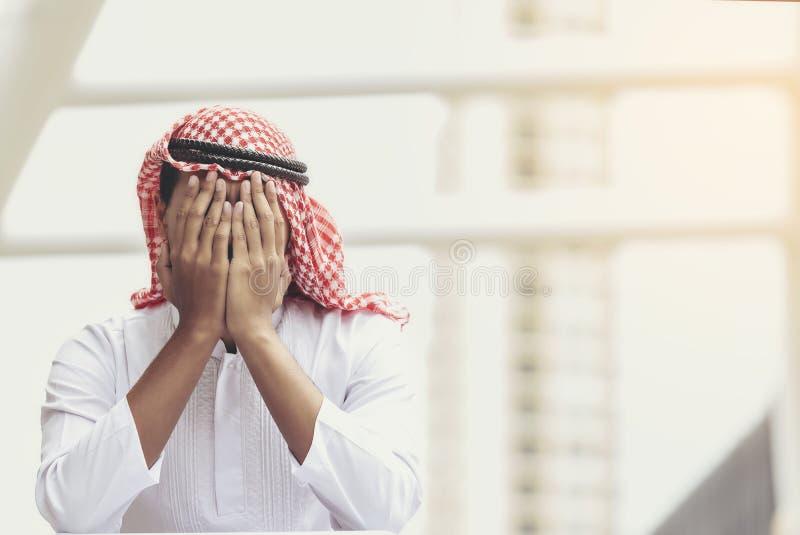 Arabiskt sammanträde för ung man med hans händer nästan hans framsida och filt royaltyfri foto