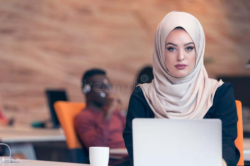 Arabska biznesowa kobieta jest ubranym hijab, pracuje w początkowym biurze fotografia stock