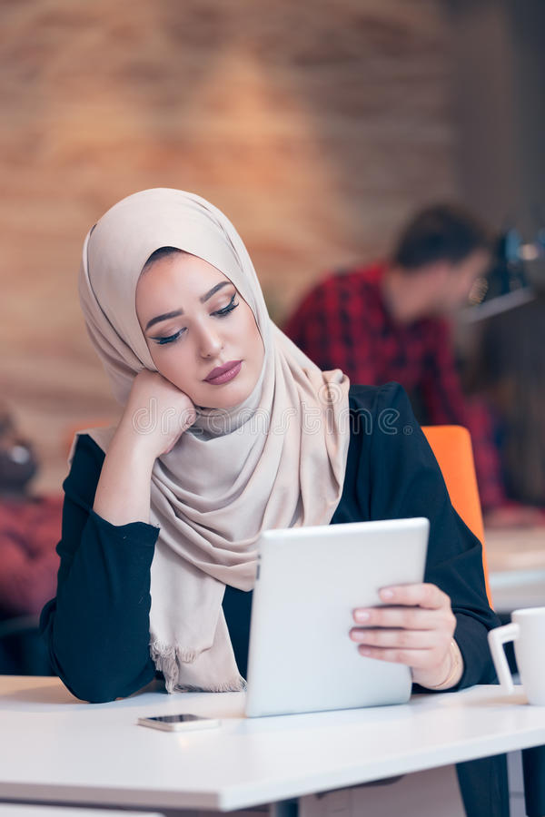 Arabska biznesowa kobieta jest ubranym hijab, pracuje w początkowym biurze obraz stock