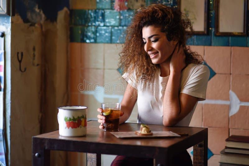 Arabska kobieta w pi?kny pr?towy patrze? przez okno fotografia stock