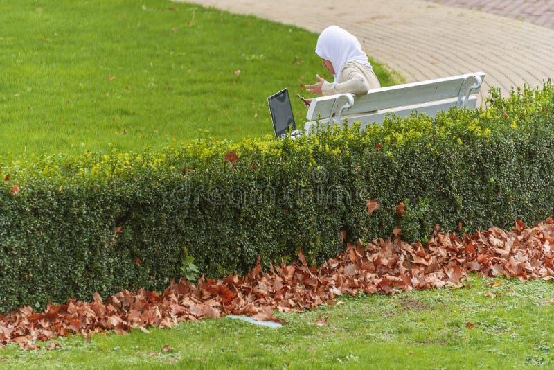 Arabska kobieta z szalika obsiadaniem w parkowym mienie laptopie i mówienie przez telefonu zdjęcie royalty free