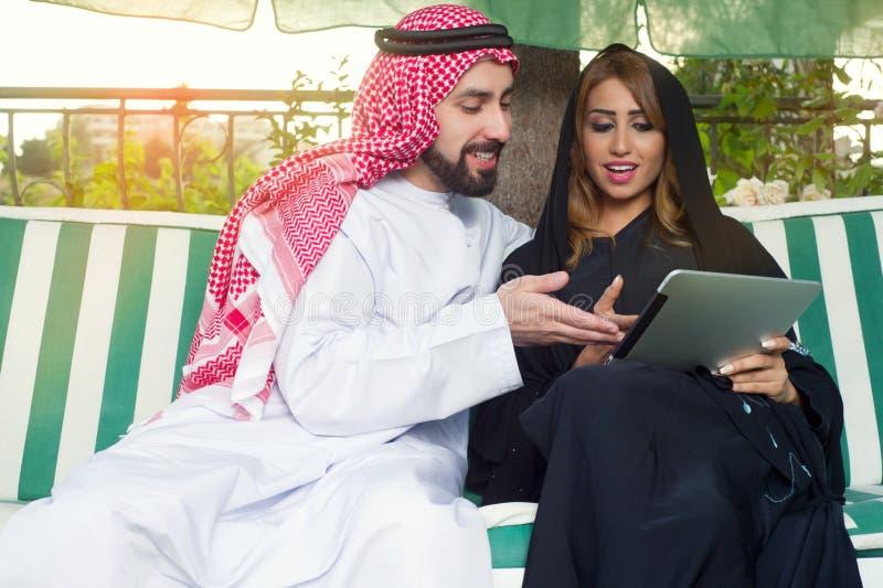 Arabska para relaksuje w ogródzie pije online & sprawdza na mobilnym ochraniaczu fotografia stock