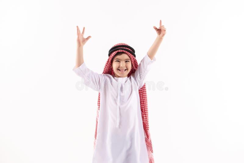 Arabska radosna chłopiec w keffiyeh stawia ręki w górę obraz royalty free
