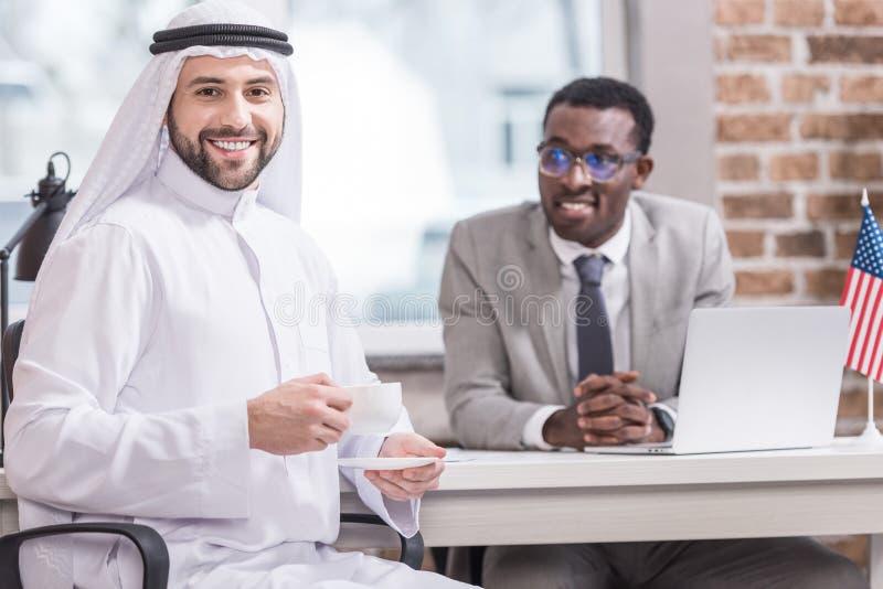 Arabski biznesmen pije kawę z amerykanin afrykańskiego pochodzenia partnerem zdjęcie royalty free