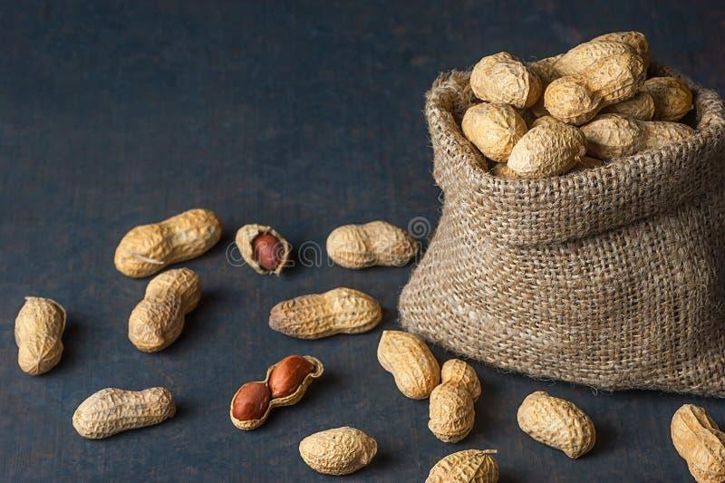 Arachide dans la coquille de noix dans le sac à toile de jute ou toile à sac sur le fond en bois composition des arachides photographie stock