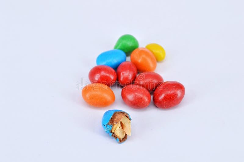 Arachide ricoperta di cioccolato su fondo bianco fotografia stock