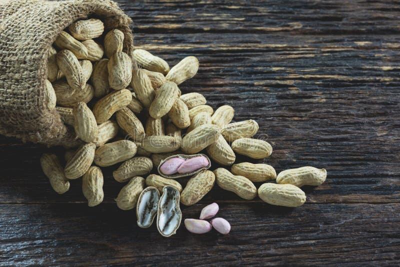 Arachides dans le sac sur la table en bois Macro d'arachide Graine d'arachides image libre de droits
