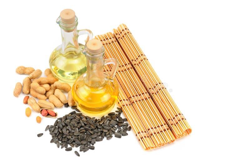 Arachidy, słonecznikowi ziarna i jarzynowi oleje odizolowywający na białych półdupkach, zdjęcia stock