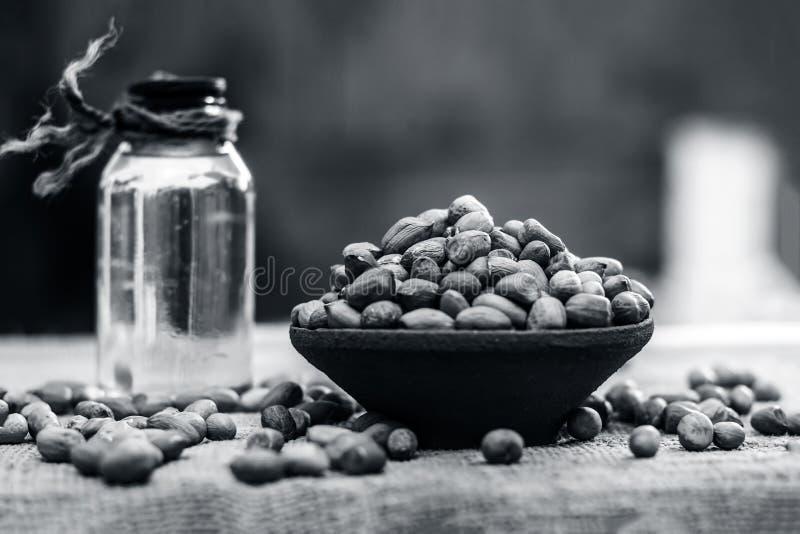 [Arachis hypogaea] arachide cruda in una ciotola dell'argilla con l'olio di arachidi su un fondo dell'iuta immagine stock