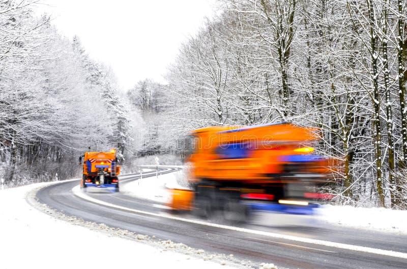 Arado de neve na estrada do inverno, veículos borrados fotografia de stock