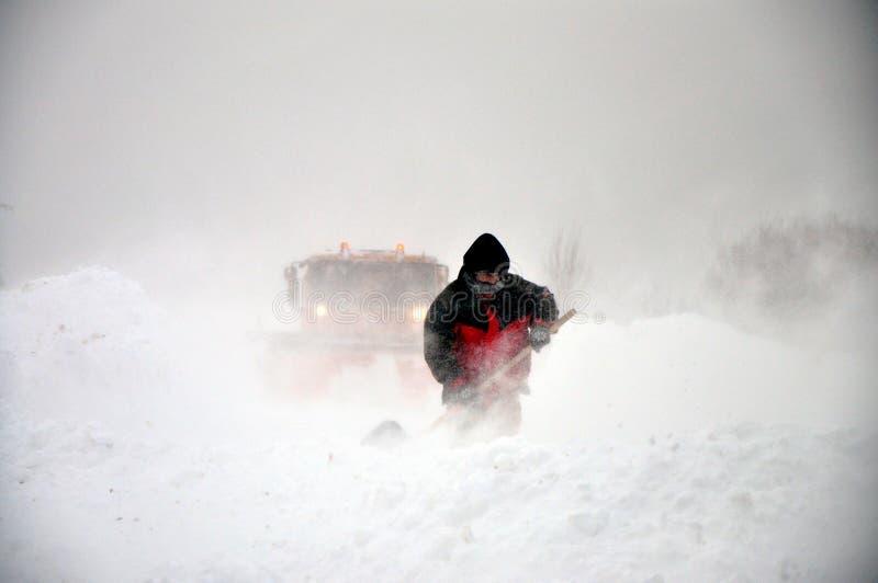 Arado e homem de neve com pá imagem de stock royalty free