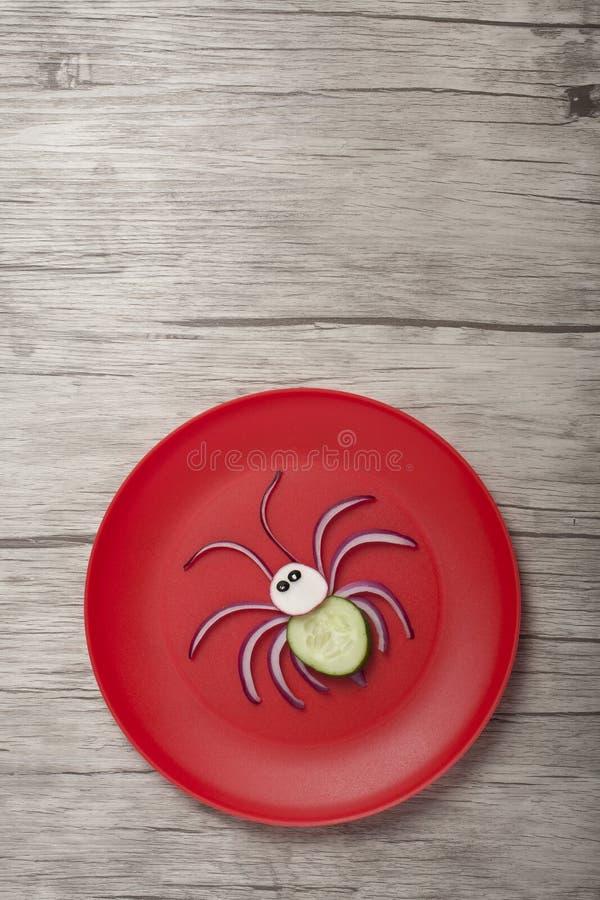 Araignée préparée avec de l'oignon et du concombre sur plaque rouge photographie stock libre de droits
