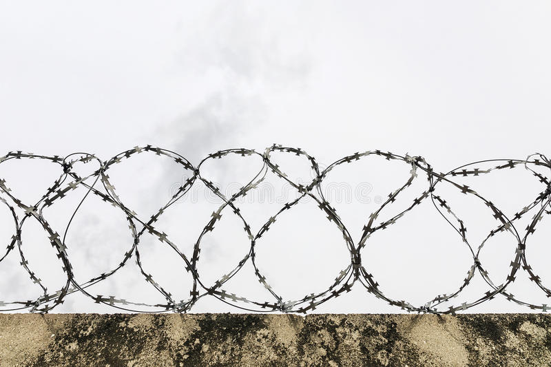 Arame farpado em uma cerca concreta foto de stock