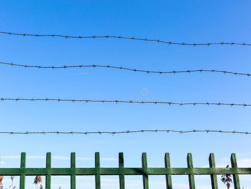 Arame farpado na cerca contra o céu azul Símbolo do unfreedom e da privação Conceito de Unfreedom fotos de stock royalty free