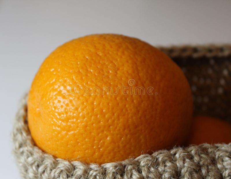 Arance arancio in un canestro della canapa su un fondo bianco fotografia stock libera da diritti