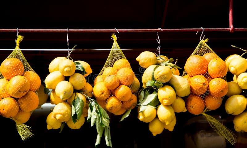 Arance e limoni che appendono nel mercato fotografia stock libera da diritti