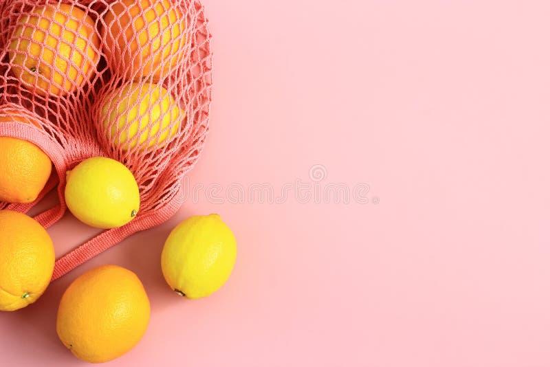 Arance e limoni nella borsa di rete riutilizzabile del cotone su fondo rosa fotografie stock