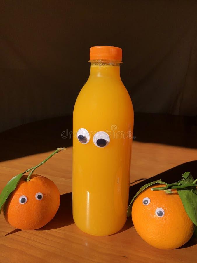 Arance e succo d'arancia Googly degli occhi Concetto creativo dell'alimento di divertimento fotografia stock