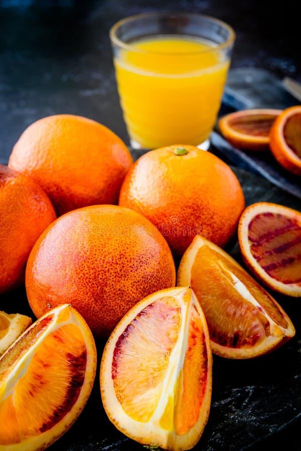 Arance sanguinelle succose fresche intere ed affettate sul piatto scuro con succo d'arancia nel fondo fotografia stock libera da diritti