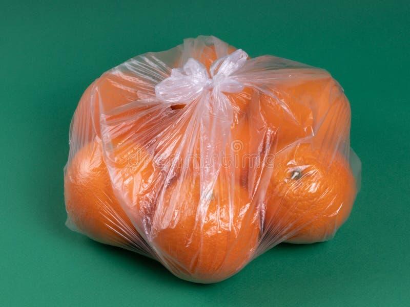 Arance in un sacchetto di plastica su un fondo verde fotografie stock libere da diritti