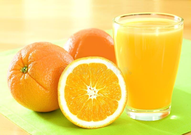 Aranci e succo di arancia immagine stock