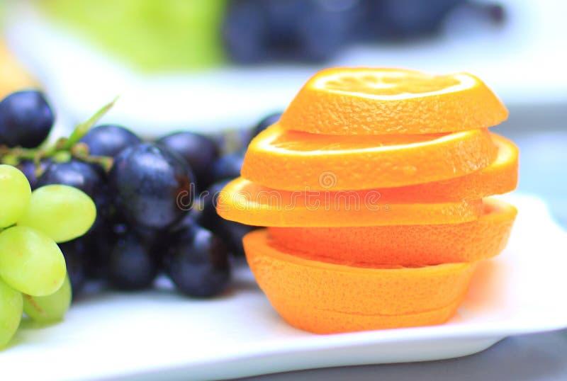 Arancia affettata con l'uva nei precedenti vari prodotti alimentari deliziosi fotografia stock