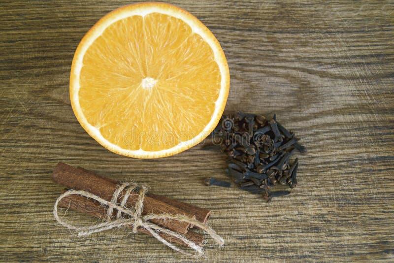 Arancia, bastoni di cannella, chiodi di garofano su fondo di legno immagini stock