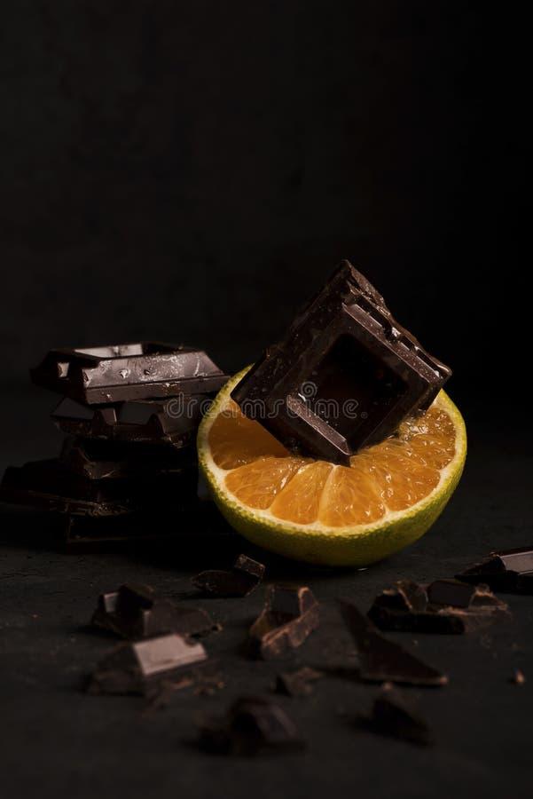 Arancia con cioccolato su fondo di legno fotografie stock