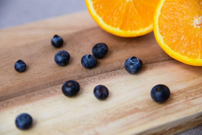 Arancia e mirtilli sul tagliere di legno fotografia stock